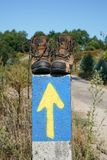 Pilgrimage on the Camino de Santiago trail, Spain. Broken walking shoes on the top of a waymark along the Way of St. James, Spain, Europe Stock Images