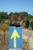 Pilgrimage on the Camino de Santiago trail, Spain. Broken walking shoes on the top of a waymark along the Way of St. James, Spain, Europe Stock Photography