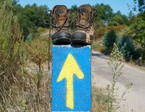 Pilgrimage on the Camino de Santiago trail, Spain. Broken walking shoes on the top of a waymark along the Way of St. James, Spain, Europe Stock Photos