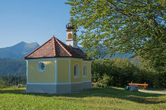Pilgrimage chapel and bench in the bavarian alps Stock Image