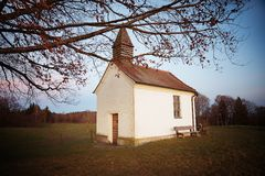 Pilgrimage chapel on the hill. View through bare leafed branches, evening mood. upper bavaria stock photography