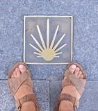 Pilgrimage to Santiago. James road sign with a few feet of a pilgrim Royalty Free Stock Photo