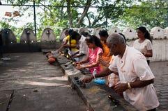 Pilgrimagers ignite coconut oil lamps Stock Photo