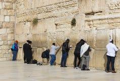 Pilgrims ber på väggen av gråta av det heliga stället av det judiska folket och mitten av dyrkan av kristen runt om arkivfoton