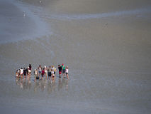 Pilgrims crossing the tidal bay at Mont Saint Michel, France Stock Photos