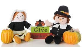 Pilgrims Give Thanks. Two happy pilgrim dolls sitting by a Give Thanks sign topped with a turkey. On a white background stock images