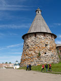 Pilgrims go by a tower of the Solovki monastery Royalty Free Stock Photos