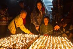 Pilgrims lighting up candles at Boudhanath stupa Stock Photos