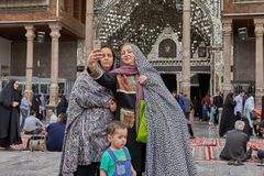Pilgrims make photos in the mosque courtyard, Tehran, Iran. Tehran, Iran - April 27, 2017: Iranian women with a child take photos against the background of The Royalty Free Stock Image