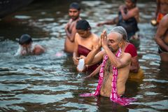 Pilgrims plunge into the water holy Ganges river in the early morning. VARANASI, INDIA - MAR 23, 2018: Pilgrims plunge into the water holy Ganges river in the stock photography