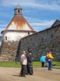 Pilgrims stand near a tower of the Solovki monastery Royalty Free Stock Image