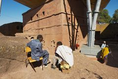 Pilgrims talk with the monolithic rock-hewn church at the background in Lalibela, Ethiopia. stock photo