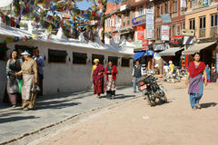 Pilgrims walk around the Bodhnath Stupa. In Kathmandu. The pilgrims spinning prayer wheels stock image