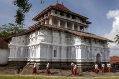 Pilgrims walk past the beautiful elephant figures on the exterior wall of the Image House at Sri Lankathilaka Rajamaha Viharaya. Royalty Free Stock Images