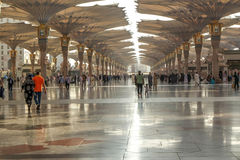 Pilgrims walk underneath giant umbrellas at Nabawi Mosque Stock Photo