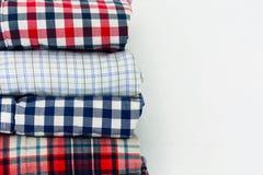 Pilha ascendente próxima de camisas de manta no fundo branco fotos de stock