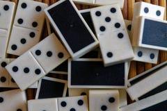 A pilha caótica do dominó remenda no fundo de madeira marrom de bambu da tabela Imagens de Stock