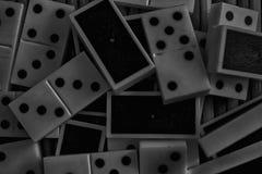 A pilha caótica monocromática do dominó remenda no fundo de madeira marrom de bambu da tabela Fotografia de Stock