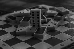 A pilha caótica monocromática do dominó remenda no fundo de madeira marrom de bambu da tabela Imagens de Stock