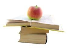 Pilha com livro e a maçã abertos imagem de stock