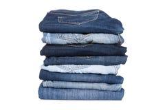 Pilha da calças das calças de brim no fundo branco imagem de stock royalty free