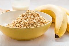 Pilha da farinha de aveia em uma bacia com banana Imagens de Stock Royalty Free