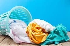 Pilha da lavanderia suja na cesta de lavagem no backgroun de madeira, azul imagem de stock