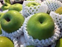 Pilha da maçã verde na rede de empacotamento da espuma do fruto branco fotografia de stock royalty free