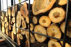 A pilha da madeira que foi cortada é colocada em uma gaiola do metal Fotografia de Stock