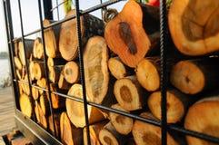 A pilha da madeira que foi cortada é colocada em uma gaiola do metal Fotos de Stock Royalty Free