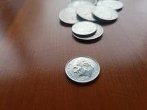 Pilha da moeda de dez centavos da liberdade da moeda dos E.U. e das outras moedas na tabela de madeira fotografia de stock