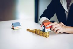 Pilha da moeda do dinheiro com casa como destinos Empréstimos para o estat real fotografia de stock royalty free