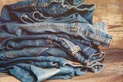 Pilha da sarja de Nimes velha das calças de brim do índigo na tabela de madeira Fotos de Stock