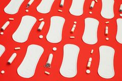 Pilha das almofadas brancas muitos tampões e comprimidos no fundo vermelho fotos de stock royalty free