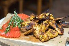 Pilha das asas de galinha grelhadas roasted na placa de madeira do carvalho imagem de stock