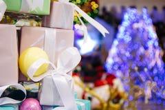 A pilha das caixas de presente decoradas na árvore de Natal com iluminação decorou a árvore de Natal no fundo Imagem de Stock