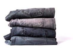 Pilha das calças de brim cinzentas isoladas no branco Imagens de Stock Royalty Free