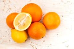 Pilha das laranjas e dos limões na tabela Fotografia de Stock