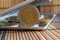 A pilha das moedas com uma denominação dianteira da moeda do baht dez no espelho reflete mentiras da carteira no fundo de bambu d Imagens de Stock