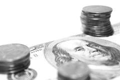 Pilha das moedas de prata sobre no close-up da nota de dólar, foto preto e branco Fotos de Stock