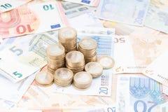 Pilha das moedas em cédulas Imagem de Stock Royalty Free