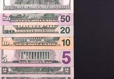 Pilha das notas de dólar de denominações diferentes no backgrond preto Fotos de Stock Royalty Free