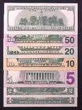 Pilha das notas de dólar de denominações diferentes no fundo preto Fotografia de Stock