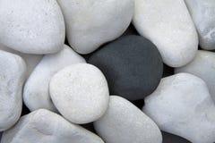 Pilha das pedras brancas e de uma pedra preta Imagens de Stock Royalty Free