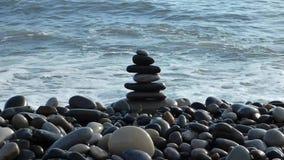 Pilha das pedras do zen na praia com ressaca do mar atrás filme