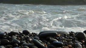 Pilha das pedras do zen na praia que quebra pela ressaca do mar video estoque