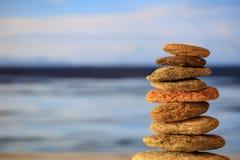 Pilha das pedras do zen no fundo do céu azul e do mar Imagens de Stock