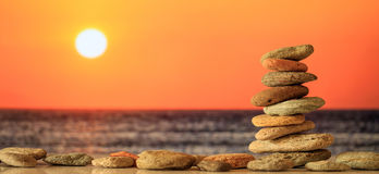 Pilha das pedras do zen no fundo do mar no por do sol Imagens de Stock Royalty Free