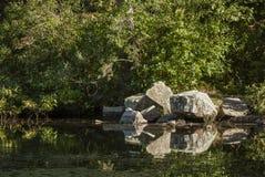 Pilha das rochas que refletem na lagoa fotos de stock royalty free