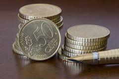 Pilha de 50 moedas e de pena dos centavos euro- Imagem de Stock Royalty Free